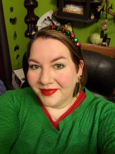 Picture of me wearing a green sweater with a red undershirt, a red and green jingle bell headband, christmas tree earrings, green eyeshadow and red lipstick.